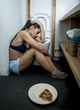 Young sad and depressed bulimic woman feeling sick guilty after vomiting pizza in WC toilet Royalty Free Stock Photo