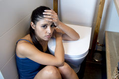 Young sad and depressed bulimic woman feeling sick sitting at the floor of the toilet leaning on WC stock photos