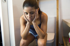 Young sad and depressed bulimic woman feeling sick sitting in toilet WC looking desperate and ill Stock Photography