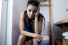 Young sad and depressed bulimic woman feeling sick sitting in toilet WC looking desperate and ill Stock Photos