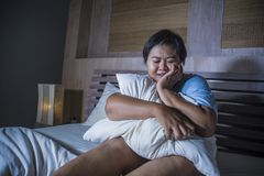 Young sad and depressed fat and chubby Asian girl feeling upset and desperate crying on bed at home victim of bullying and. Discrimination for her plus size and royalty free stock image