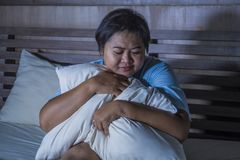 Young sad and depressed fat and chubby Asian girl feeling upset and desperate crying on bed at home victim of bullying and. Discrimination for her plus size and stock photos