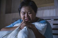 Young sad and depressed fat and chubby Asian girl feeling upset and desperate crying on bed at home victim of bullying and. Discrimination for her plus size and stock photo