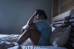 Young sad and depressed fat and chubby Asian girl feeling upset and desperate crying on bed at home victim of bullying and. Discrimination for her plus size and royalty free stock photo