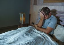 Young sad and depressed sleepless man lying on bed worried and thoughtful at home bedroom suffering depression problem feeling. Unwell and desperate broken royalty free stock photo