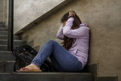 Depressed student woman or bullied teenager girl sitting outdoors on street staircase scared and anxious victim of bullying. Young sad and depressed student stock photo