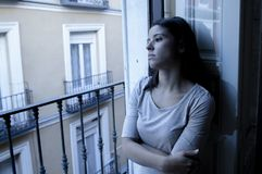 Young sad and desperate Latin woman at home balcony looking destroyed and depressed suffering depression feeling lonely unhappy Royalty Free Stock Image