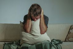 Young sad and desperate man at home sitting at sofa couch covering face with hands and pillow crying suffering depression and stre. Young sad and desperate man Royalty Free Stock Photo