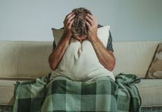 Young sad and desperate man at home sitting at sofa couch covering face with hands and pillow crying suffering depression and stre. Young sad and desperate man Stock Photos