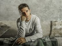 Young sad and desperate man at home sitting at sofa couch suffering depression and stress feeling miserable in frustration concept. Young sad and desperate man Stock Photography