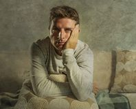 Young sad and desperate man at home sitting at sofa couch suffering depression and stress feeling miserable in frustration concept. Young sad and desperate man Stock Image