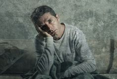 Young sad and desperate man at home sitting at sofa couch suffering depression and stress feeling miserable in frustration concept. Young sad and desperate man Stock Images