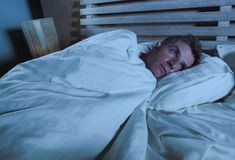 Young sad and desperate man lying on bed crying depressed looking away thoughtful and pensive suffering depression problem and str royalty free stock photography