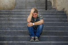 Young sad and desperate man sitting outdoors at street stairs suffering anxiety and depression feeling miserable crying in. Young sad and desperate man sitting royalty free stock image