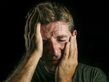 Young sad and devastated man crying desperate covering face with his hands feeling stressed and lost suffering pain and depression. Isolated on black background stock image
