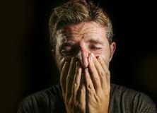 Young sad and devastated man crying desperate covering face with his hands feeling stressed and lost suffering pain and depression. Isolated on black background stock images