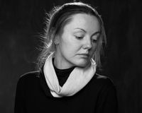 Young sad disoriented woman. Portrait of a young sad woman, looking down, grey background Stock Photos