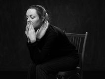 Young sad disoriented woman sitting on the chair. Portrait of a young sad disoriented woman sitting on the chair, side view , grey background Royalty Free Stock Photography