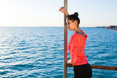 Young sad female standing alone on the pier and pensive looking down on the sea waves Stock Images