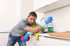 Young sad frustrated man washing and cleaning home kitchen sink. Young sad man cleaning with detergent spray and sponge washing and making home kitchen sink stock images