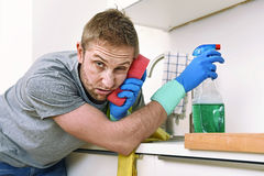 Young sad frustrated man washing and cleaning home kitchen sink stock photo