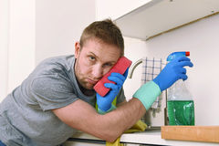 Young sad frustrated man washing and cleaning home kitchen sink stock images