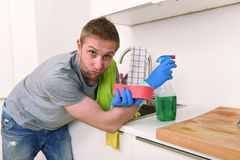 Young sad frustrated man washing and cleaning home kitchen sink. Young sad man cleaning with detergent spray and sponge washing and making home kitchen sink royalty free stock images