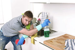 Young sad frustrated man washing and cleaning home kitchen sink. Young sad man cleaning with detergent spray and sponge washing and making home kitchen sink stock photos