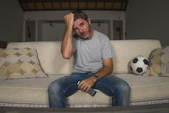 Young sad and frustrated soccer fan man watching football game on television at living room couch frustrated and desperate because royalty free stock image