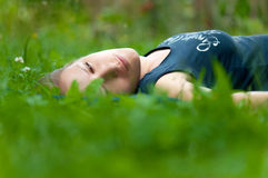 Young sad girl. Lying outdoors in grass Stock Photography