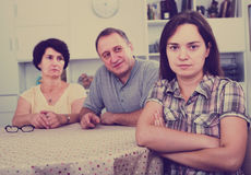 Young sad girl is annoyed by her retiree parents. And sitting back to them indoors Royalty Free Stock Image