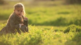 Young sad girl lonely in grass field. A young girl is sitting picking grass alone in a grass field, frustrated or sad