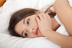 Young sad girl lying in bed. Stock Photos