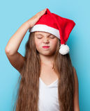 Young sad girl in Santas hat. On blue background Stock Photos