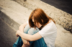 Young sad girl sitting on asphalt Stock Photo