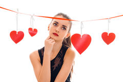 Young sad girl standing near the Red Ribbon with hearts holding a hand near the face and looks toward. Isolated on white Royalty Free Stock Photography