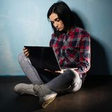 Young sad girl suffering from dependence on social networks sitting on the floor with a notebook.  royalty free stock photos