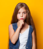 Young sad girl. On yellow background Stock Photography