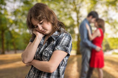 Young sad jealousy girl seeing her boyfriend flirting with another woman Stock Images