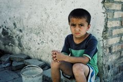 Young sad looking boy waiting on a street corner to collect some water from the community reserve stock photos