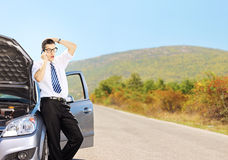 Young sad male on a broken car talking on a cell phone Royalty Free Stock Image