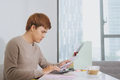 Young sad man analyzing home finances while gesturing with hand. And looking at documents. Sitting near table with tablet Royalty Free Stock Image