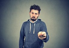 Upset man pointing at camera in accusation. Young sad man with beard pointing at camera indicating guilt and blaming in anger Royalty Free Stock Photography