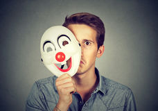 Young sad man hiding behind happy clown mask Royalty Free Stock Photography
