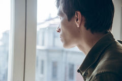 Young sad man looking out the window Royalty Free Stock Photos