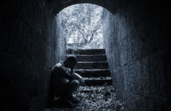 Young sad man sitting inside of dark stone tunnel Royalty Free Stock Image