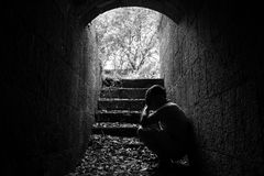 Young sad man sitting inside of dark tunnel Stock Photo