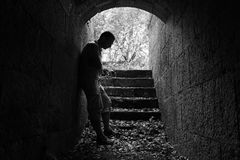 Young sad man stands in dark stone tunnel Royalty Free Stock Images