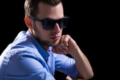 Young sad man in sunglasses thinking about something over black Royalty Free Stock Image