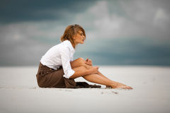 Young sad and pensive woman sits on sand in desert. Royalty Free Stock Photo